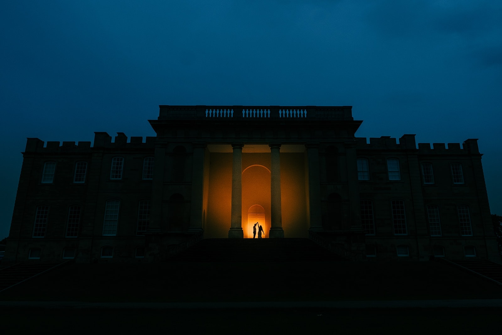 Leigh twirls Yasmin on the entrance of Kimbolton Castle at night