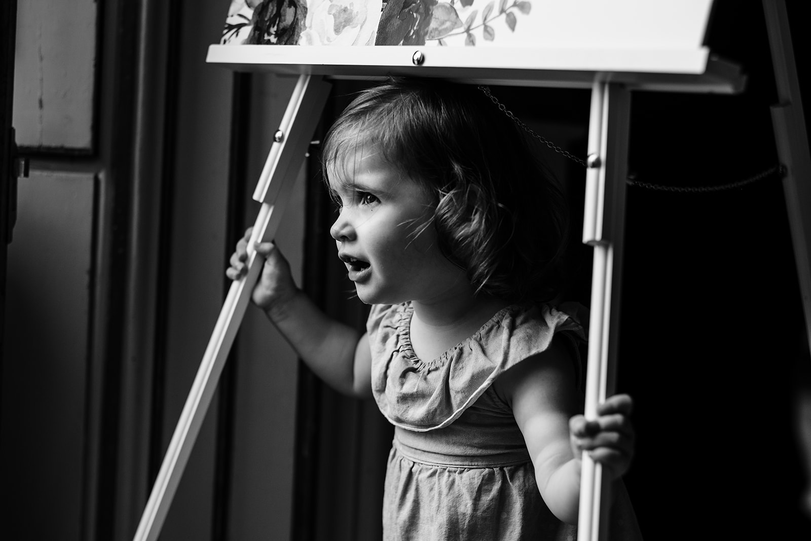 Little girl playing under the table plan sign