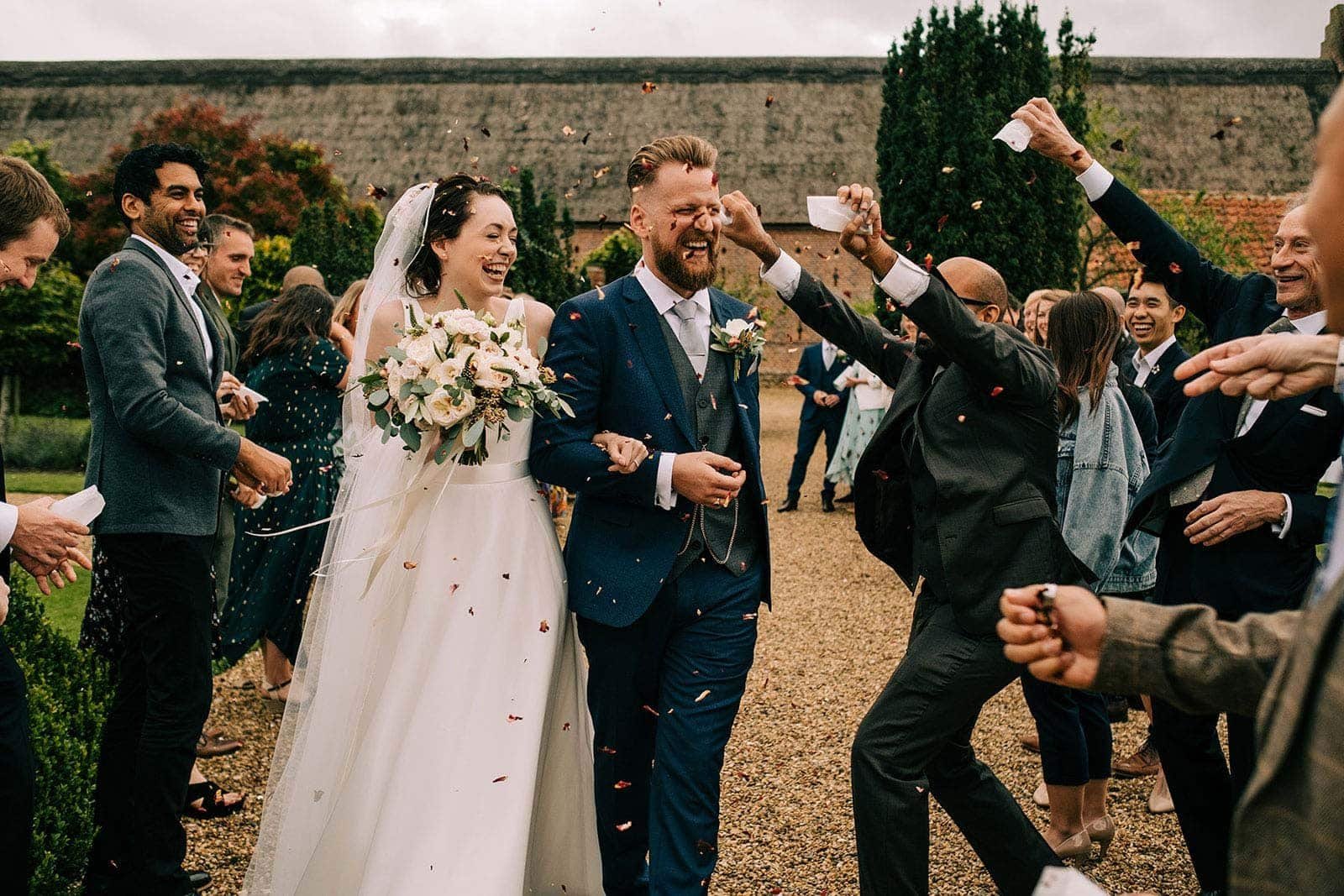 Bride and groom get covered in confetti at Hales Hall