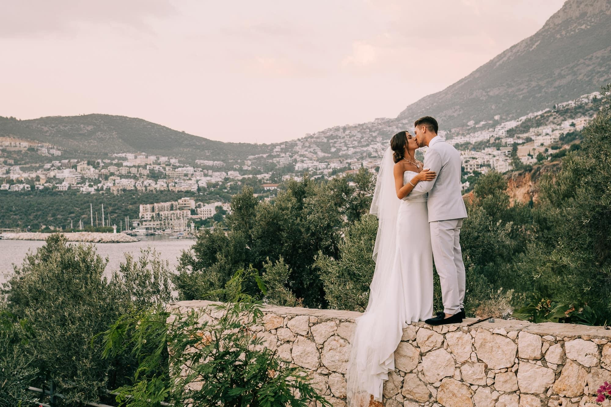 Bride and groom standing on a wall overlooking the Kalkan coastline