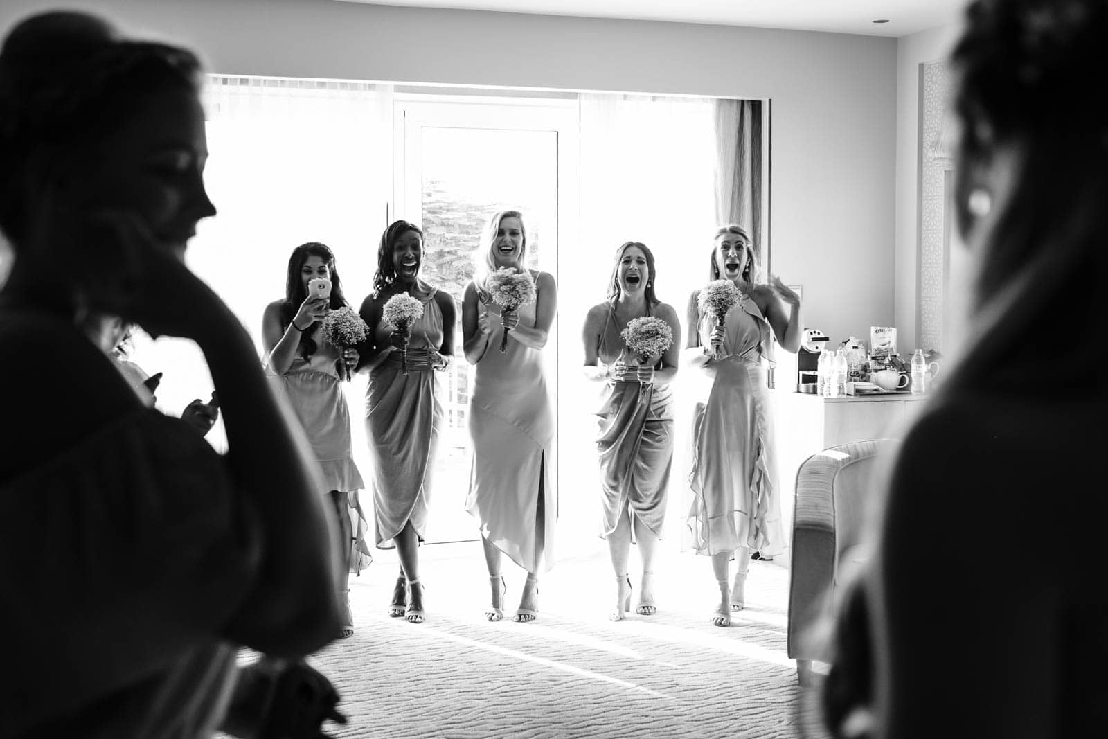 Bridesmaids react to the bride in her dress