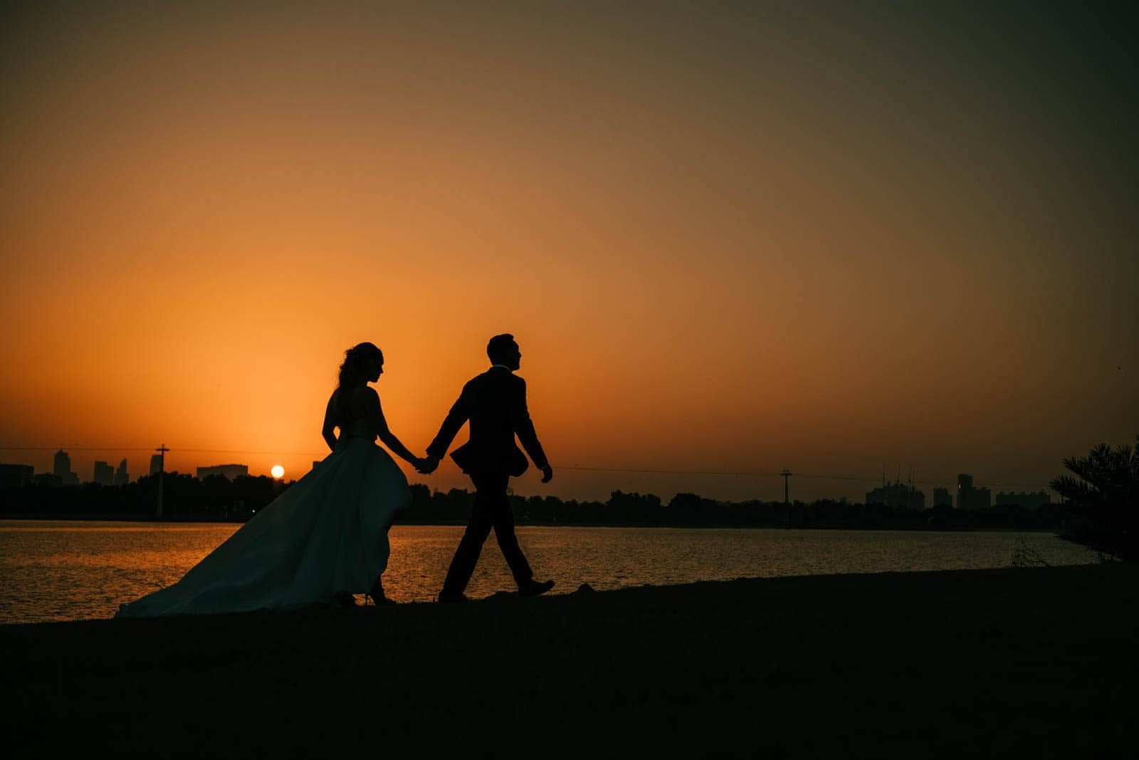 Bride and groom walk along the river during sunset at Park Hyatt Dubai