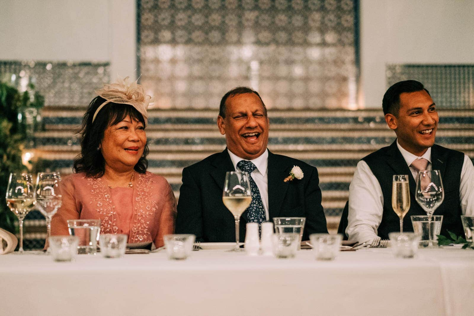 Grooms dad and mum laugh during the best man speech