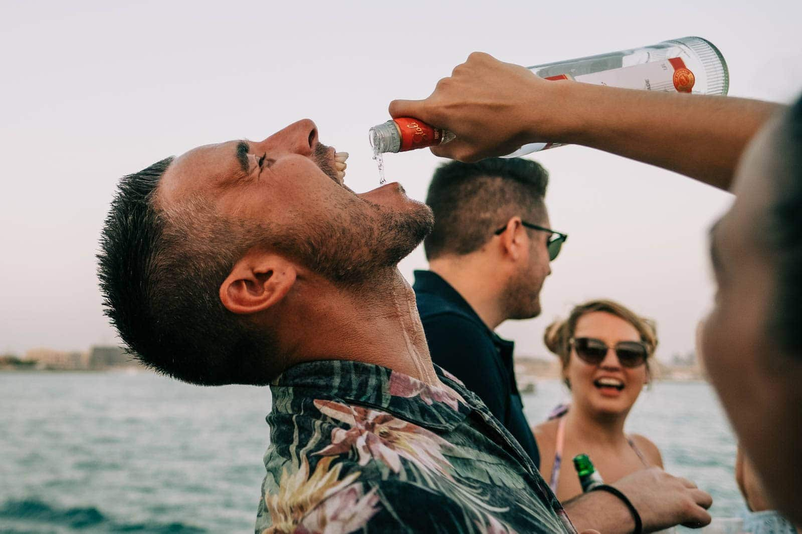 Groomsmen has Vodka poured into his mouth