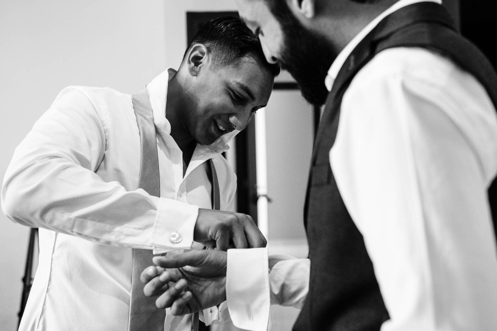 Groom helps best man with his cuff links