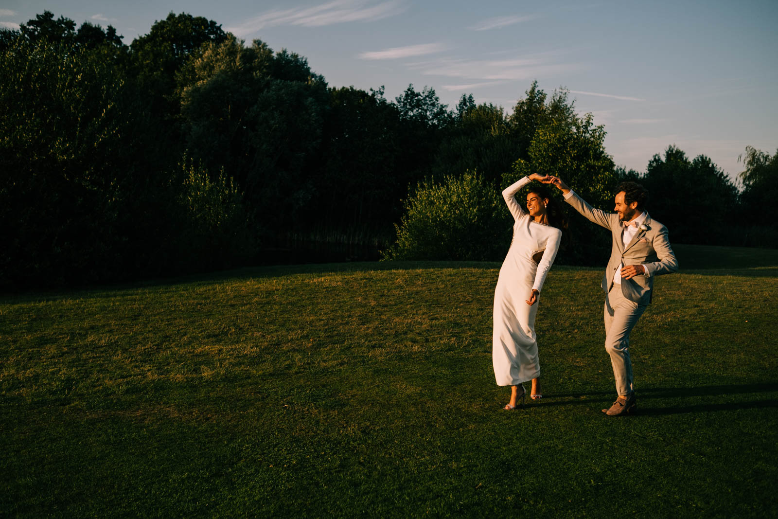 Bride and groom dancing in the sun