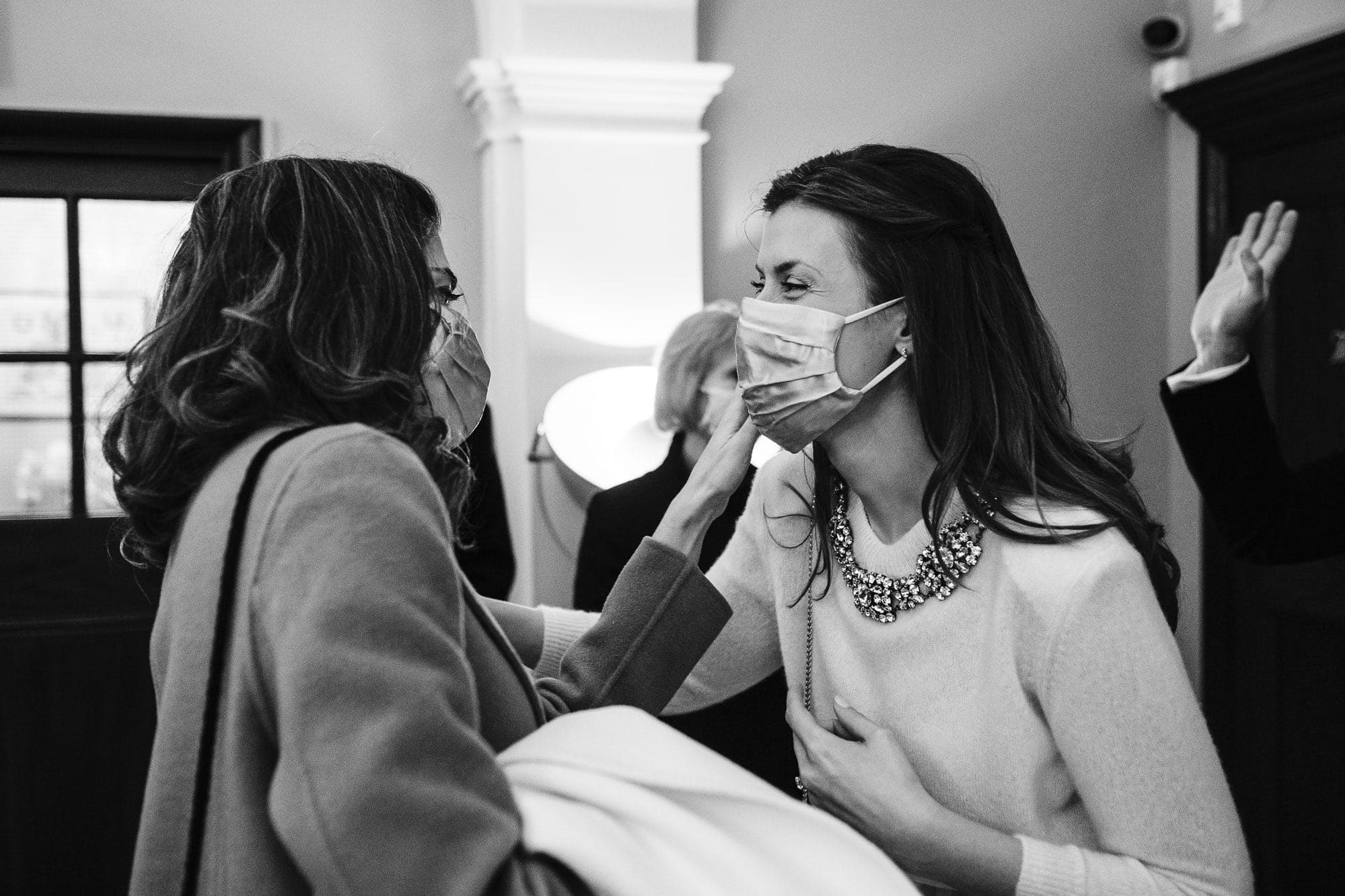 Bride's mum adjusts her mask before the wedding ceremony