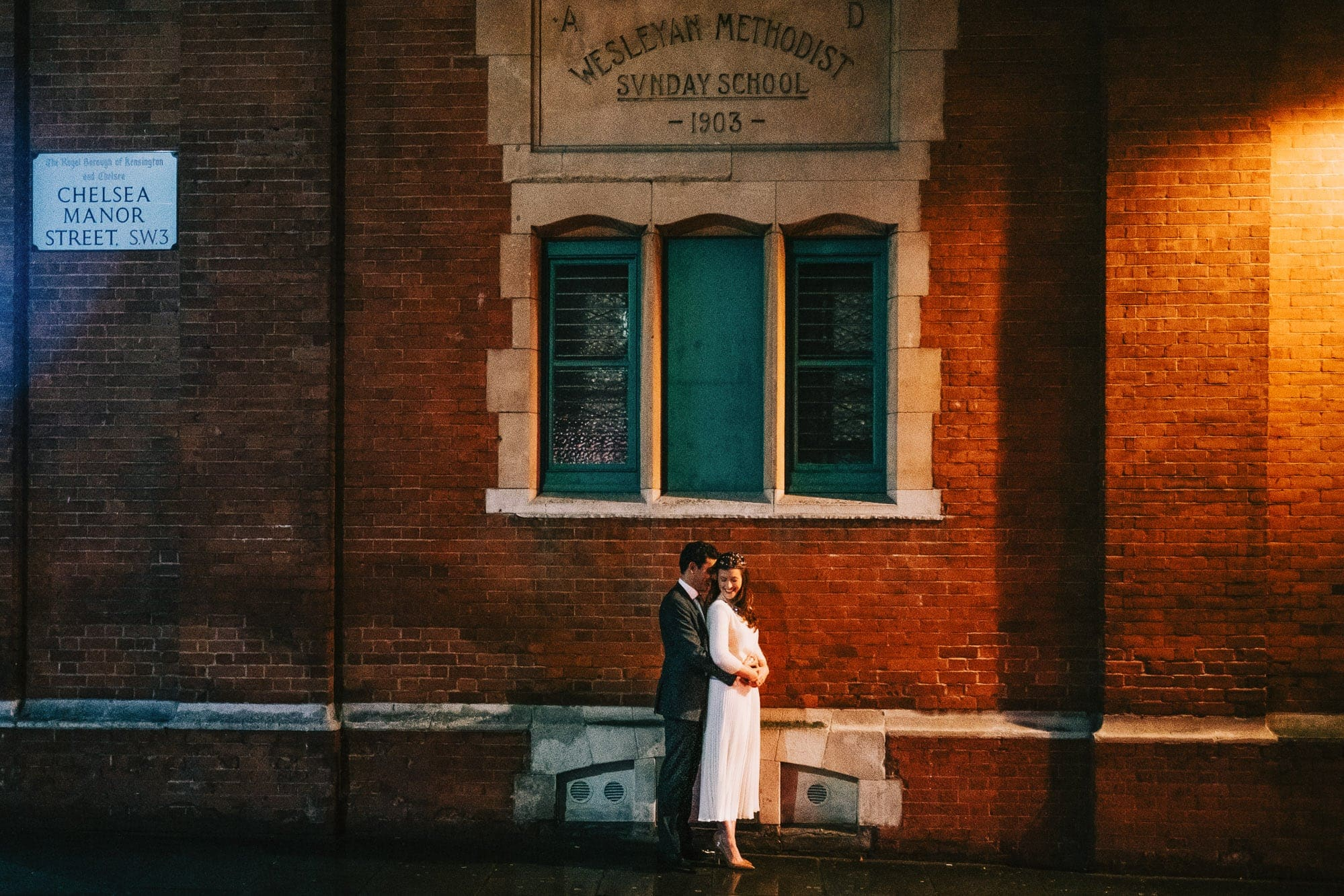 Bride and groom cuddling under the evening light outside the Chelsea Town Hall