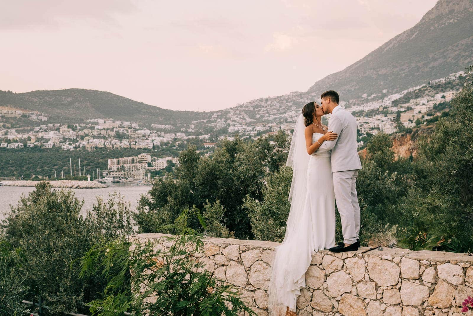 Bride and groom kiss with the incredible Ibiza scenery in the background