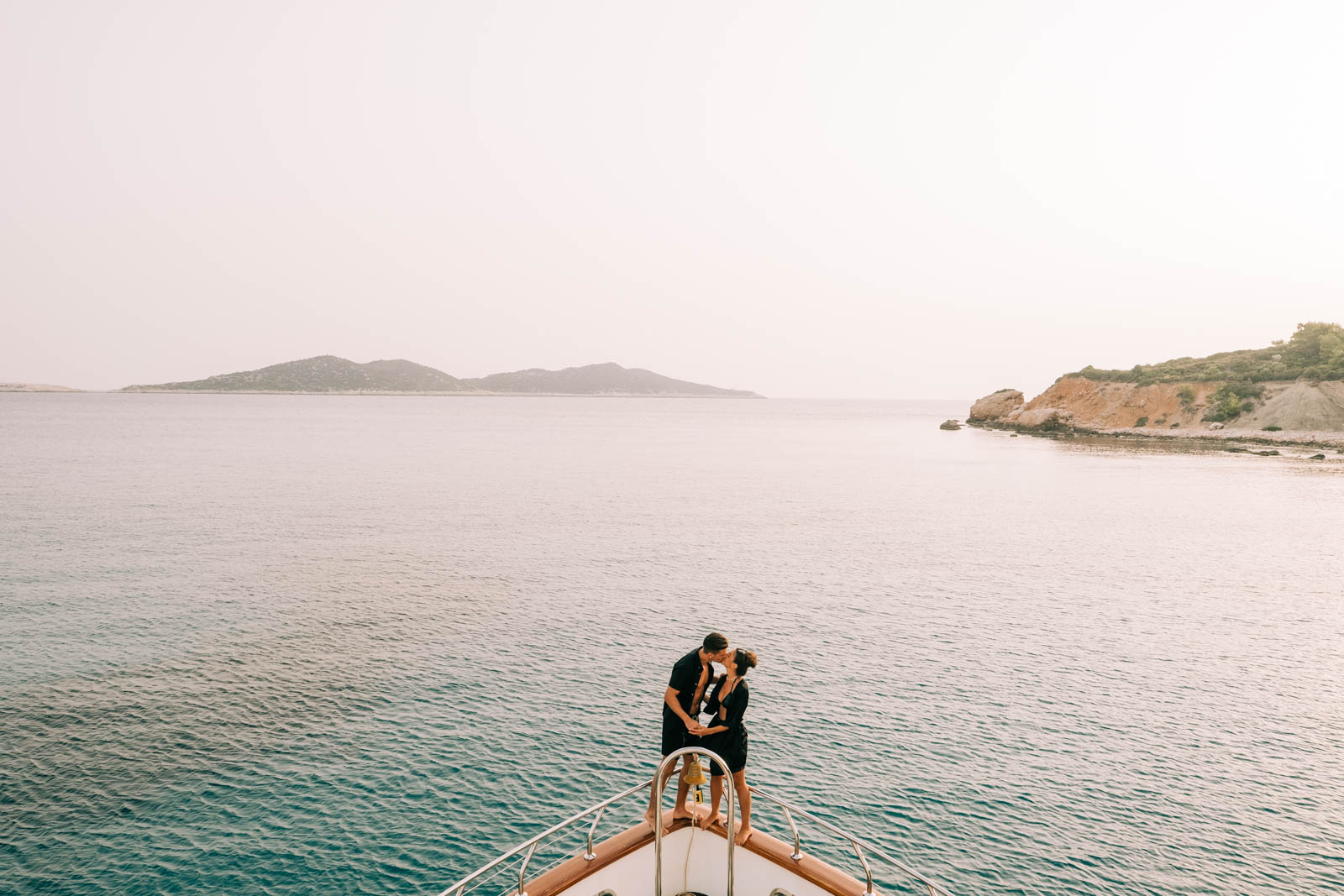 Bride and groom kiss on a boat of the coast of Ibiza