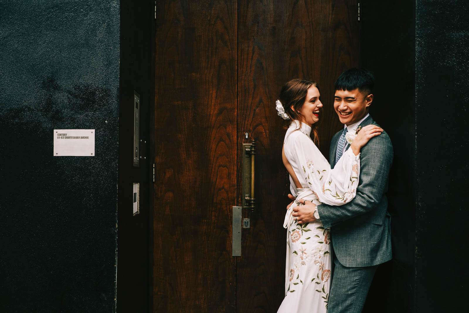 Bride and groom at the Century Club entrance in London